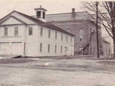 Fireman's Hall, corner of Main and Park Street, Potsdam, NY. In the background is the Town Hall and Opera House. The current fire station was built in the early 1900s and made of brick. The wooden building in this picture from the museum's website is not dated.